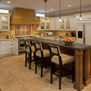 This is an example of a large mediterranean l-shaped open plan kitchen in Orange County with white cabinets, beige splashback, beige floor, limestone splashback, limestone floors, with island, a farmhouse sink, recessed-panel cabinets, limestone benchtops, stainless steel appliances and beige benchtop.