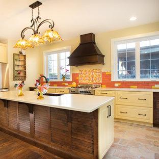 ワシントンD.C.の中サイズの地中海スタイルのおしゃれなキッチン (エプロンフロントシンク、レイズドパネル扉のキャビネット、黄色いキャビネット、マルチカラーのキッチンパネル、シルバーの調理設備、セラミックタイルのキッチンパネル、レンガの床、茶色い床、クオーツストーンカウンター、白いキッチンカウンター) の写真