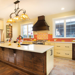 Photo of a mid-sized mediterranean l-shaped eat-in kitchen in DC Metro with a farmhouse sink, raised-panel cabinets, yellow cabinets, multi-coloured splashback, stainless steel appliances, with island, ceramic splashback, brick floors, brown floor, quartz benchtops and white benchtop.