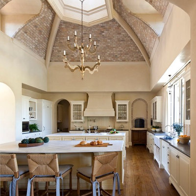 Example of a huge tuscan l-shaped medium tone wood floor and brown floor eat-in kitchen design in Phoenix with a farmhouse sink, glass-front cabinets, white cabinets, solid surface countertops, white backsplash, subway tile backsplash, stainless steel appliances and an island
