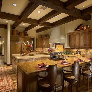 Inredning av ett medelhavsstil stort, avskilt l-kök, med en köksö, skåp i mellenmörkt trä, kaklad bänkskiva, flerfärgad stänkskydd, stänkskydd i keramik, integrerade vitvaror, en rustik diskho, mörkt trägolv och luckor med upphöjd panel