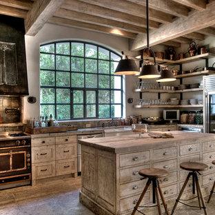 ヒューストンの大きい地中海スタイルのおしゃれなキッチン (シルバーの調理設備の、木材カウンター、エプロンフロントシンク、シェーカースタイル扉のキャビネット、ヴィンテージ仕上げキャビネット、メタリックのキッチンパネル、メタルタイルのキッチンパネル、茶色いキッチンカウンター) の写真
