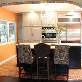 Immagine di una cucina mediterranea di medie dimensioni con lavello a doppia vasca, ante con bugna sagomata, ante grigie, elettrodomestici in acciaio inossidabile e penisola
