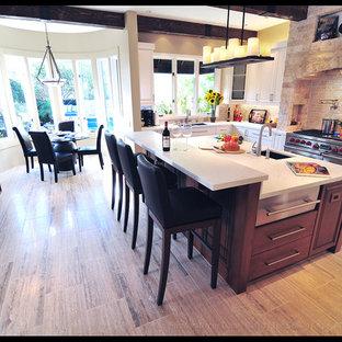 Idee per una grande cucina a L stile rurale chiusa con lavello a doppia vasca, ante con bugna sagomata, ante bianche, top in marmo, paraspruzzi beige, paraspruzzi con piastrelle in pietra, elettrodomestici in acciaio inossidabile, parquet chiaro e isola