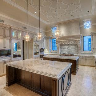 Idéer för mycket stora medelhavsstil kök, med en rustik diskho, luckor med infälld panel, beige skåp, marmorbänkskiva, beige stänkskydd, stänkskydd i mosaik, integrerade vitvaror, travertin golv och flera köksöar