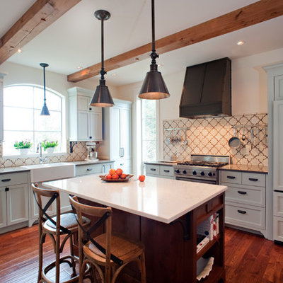 Tuscan l-shaped kitchen photo in Vancouver with a farmhouse sink, shaker cabinets, gray cabinets, beige backsplash and paneled appliances