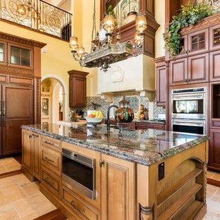Esempio di un'ampia cucina mediterranea con ante con bugna sagomata, ante in legno bruno, top in granito, paraspruzzi multicolore, pavimento in travertino, isola, pavimento beige, elettrodomestici da incasso e top multicolore