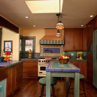 オレンジカウンティの地中海スタイルのおしゃれなキッチン (エプロンフロントシンク、マルチカラーのキッチンパネル、タイルカウンター、落し込みパネル扉のキャビネット、濃色木目調キャビネット、パネルと同色の調理設備、マルチカラーのキッチンカウンター) の写真
