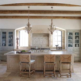 オレンジカウンティの中サイズの地中海スタイルのおしゃれなキッチン (ガラス扉のキャビネット、ベージュのキャビネット、ベージュキッチンパネル、パネルと同色の調理設備、エプロンフロントシンク、珪岩カウンター、ライムストーンの床、ライムストーンの床、ベージュの床) の写真