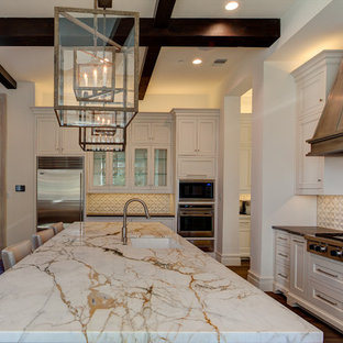 This is an example of an expansive mediterranean l-shaped eat-in kitchen in Dallas with an undermount sink, recessed-panel cabinets, white cabinets, marble benchtops, white splashback, terra-cotta splashback, stainless steel appliances, light hardwood floors and with island.