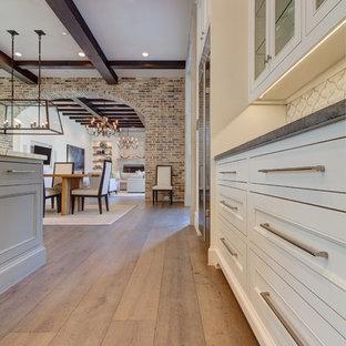 Geräumige Mediterrane Wohnküche in L-Form mit Unterbauwaschbecken, Schrankfronten mit vertiefter Füllung, weißen Schränken, Küchenrückwand in Weiß, Rückwand aus Terrakottafliesen, Küchengeräten aus Edelstahl, hellem Holzboden und Kücheninsel in Dallas