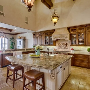 Photo of an expansive mediterranean u-shaped open plan kitchen in San Diego with a belfast sink, raised-panel cabinets, medium wood cabinets, granite worktops, beige splashback, stone tiled splashback, integrated appliances, limestone flooring, an island, brown floors and multicoloured worktops.