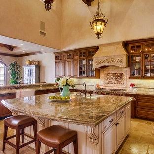 サンディエゴの巨大な地中海スタイルのおしゃれなキッチン (エプロンフロントシンク、レイズドパネル扉のキャビネット、中間色木目調キャビネット、御影石カウンター、ベージュキッチンパネル、石タイルのキッチンパネル、ライムストーンの床、パネルと同色の調理設備、茶色い床、マルチカラーのキッチンカウンター) の写真