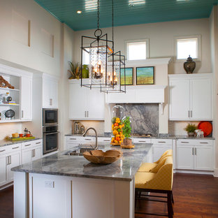 Kitchen - mediterranean l-shaped dark wood floor kitchen idea in Other with a double-bowl sink, recessed-panel cabinets, white cabinets, multicolored backsplash, stainless steel appliances and an island