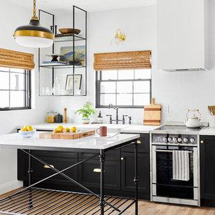 ロサンゼルスの小さい地中海スタイルのおしゃれなキッチン (エプロンフロントシンク、シェーカースタイル扉のキャビネット、黒いキャビネット、クオーツストーンカウンター、白いキッチンパネル、シルバーの調理設備の、淡色無垢フローリング、白いキッチンカウンター、サブウェイタイルのキッチンパネル) の写真