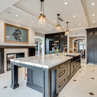 Inspiration for an expansive mediterranean galley eat-in kitchen in Other with a farmhouse sink, beaded inset cabinets, black cabinets, quartz benchtops, beige splashback, marble splashback, black appliances, marble floors, with island, multi-coloured floor and beige benchtop.