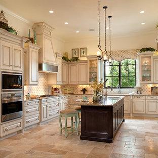 オーランドの広い地中海スタイルのおしゃれなキッチン (レイズドパネル扉のキャビネット、白いキャビネット、マルチカラーのキッチンパネル、シルバーの調理設備、ベージュの床、御影石カウンター、セラミックタイルのキッチンパネル、トラバーチンの床) の写真