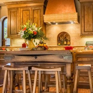 Bild på ett litet medelhavsstil kök, med en rustik diskho, skåp i shakerstil, skåp i mellenmörkt trä, bänkskiva i betong, beige stänkskydd, stänkskydd i stenkakel, rostfria vitvaror, mellanmörkt trägolv och en köksö