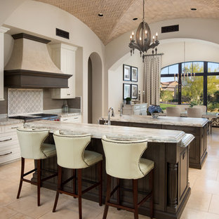 This is an example of an expansive mediterranean u-shaped open plan kitchen in Phoenix with a farmhouse sink, raised-panel cabinets, brown cabinets, quartzite benchtops, multi-coloured splashback, porcelain splashback, stainless steel appliances, porcelain floors, multiple islands, beige floor and multi-coloured benchtop.