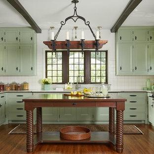ミネアポリスの地中海スタイルのおしゃれなキッチン (アンダーカウンターシンク、落し込みパネル扉のキャビネット、緑のキャビネット、白いキッチンパネル、シルバーの調理設備の、無垢フローリング、茶色い床、白いキッチンカウンター) の写真