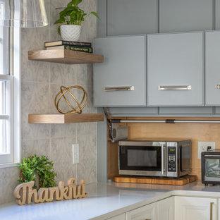 Inredning av ett maritimt mellanstort vit vitt kök, med en rustik diskho, luckor med infälld panel, vita skåp, bänkskiva i kvartsit, flerfärgad stänkskydd, stänkskydd i porslinskakel, rostfria vitvaror, mellanmörkt trägolv, en köksö och brunt golv