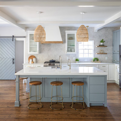 Mid-sized beach style l-shaped medium tone wood floor and brown floor open concept kitchen photo in Raleigh with a farmhouse sink, recessed-panel cabinets, white cabinets, quartzite countertops, multicolored backsplash, porcelain backsplash, stainless steel appliances, an island and white countertops