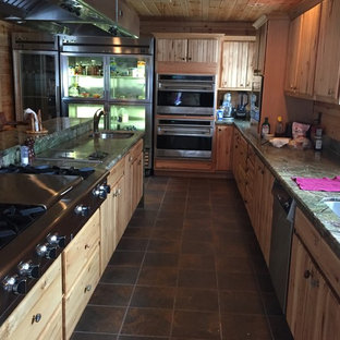 Large country l-shaped eat-in kitchen in Other with a double-bowl sink, louvered cabinets, light wood cabinets, granite benchtops, stainless steel appliances, slate floors, with island and multi-coloured floor.