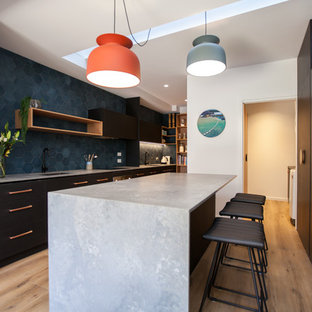 Mid-sized contemporary u-shaped eat-in kitchen in Hobart with black cabinets, solid surface benchtops, blue splashback, stainless steel appliances, light hardwood floors, with island and an undermount sink.