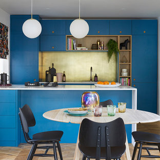 Photo of a contemporary galley kitchen in Melbourne with flat-panel cabinets, blue cabinets, metallic splashback, panelled appliances, medium hardwood floors, a peninsula, brown floor and white benchtop.