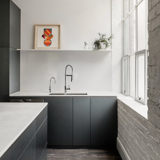 This is an example of a contemporary kitchen in Melbourne with a double-bowl sink, flat-panel cabinets, grey cabinets, white splashback, dark hardwood floors, brown floor and white benchtop.