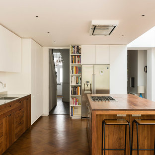 Inspiration for a medium sized contemporary u-shaped kitchen/diner in London with flat-panel cabinets, stainless steel appliances, medium hardwood flooring, an island, brown floors, an integrated sink, medium wood cabinets, wood worktops and brown worktops.