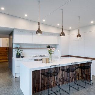 Foto de cocina de galera, minimalista, con armarios con paneles lisos, puertas de armario blancas, salpicadero blanco, electrodomésticos de acero inoxidable, suelo de terrazo, una isla y suelo gris