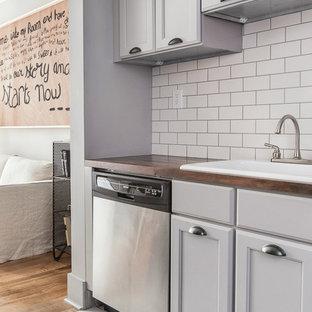 ニューヨークの小さいエクレクティックスタイルのおしゃれなキッチン (ドロップインシンク、シェーカースタイル扉のキャビネット、グレーのキャビネット、白いキッチンパネル、サブウェイタイルのキッチンパネル、シルバーの調理設備の、セラミックタイルの床、木材カウンター) の写真