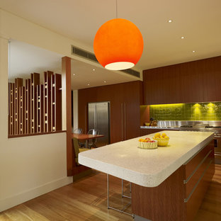 Mid-sized trendy l-shaped medium tone wood floor eat-in kitchen photo in Sydney with stainless steel appliances, flat-panel cabinets, dark wood cabinets, green backsplash, ceramic backsplash, granite countertops and an island