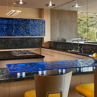 Design ideas for a modern u-shaped eat-in kitchen in Phoenix with an integrated sink, glass-front cabinets, blue cabinets, glass benchtops, black splashback, stone slab splashback and stainless steel appliances.