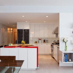 Offene, Mittelgroße Nordische Küche in L-Form mit Unterbauwaschbecken, flächenbündigen Schrankfronten, weißen Schränken, Mineralwerkstoff-Arbeitsplatte, Küchenrückwand in Weiß, Glasrückwand, Küchengeräten aus Edelstahl, hellem Holzboden, Kücheninsel und roter Arbeitsplatte in New York