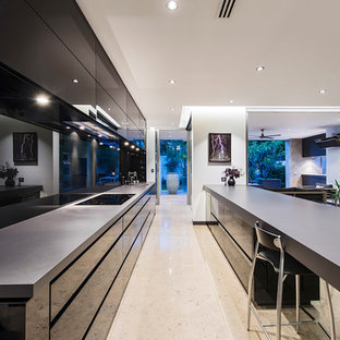 Huge contemporary open concept kitchen remodeling - Inspiration for a huge contemporary galley travertine floor open concept kitchen remodel in Perth with flat-panel cabinets, black cabinets, black backsplash, glass sheet backsplash, stainless steel appliances, a peninsula and a drop-in sink
