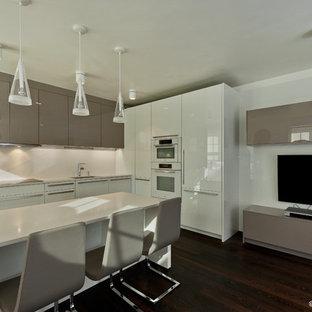 Immagine di una cucina minimalista di medie dimensioni con lavello sottopiano, ante lisce, ante marroni, elettrodomestici in acciaio inossidabile, parquet scuro e isola