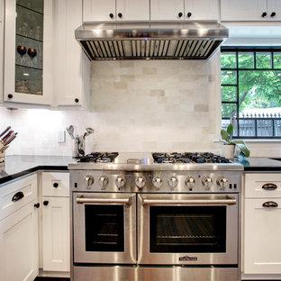Offene, Zweizeilige, Geräumige Klassische Küche mit Waschbecken, Schrankfronten im Shaker-Stil, weißen Schränken, Granit-Arbeitsplatte, Küchenrückwand in Weiß, Rückwand aus Travertin, Küchengeräten aus Edelstahl, Bambusparkett, Kücheninsel, braunem Boden und schwarzer Arbeitsplatte in Houston