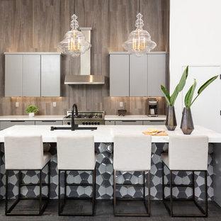 Idée de décoration pour une cuisine marine avec un évier encastré, un placard à porte plane, des portes de placard marrons, une crédence marron, un électroménager en acier inoxydable, un sol en bois foncé, un îlot central et un plan de travail blanc.