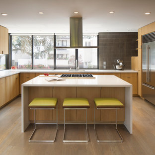 Design ideas for a midcentury kitchen in San Francisco with an undermount sink, flat-panel cabinets, light wood cabinets, quartz benchtops, glass tile splashback, stainless steel appliances, light hardwood floors, with island and brown splashback.