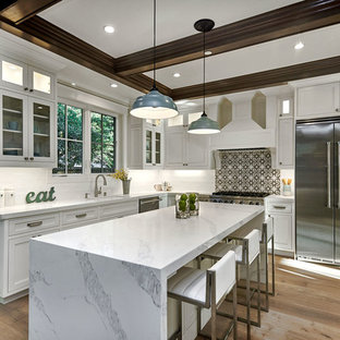 Mid-sized transitional kitchen appliance - Example of a mid-sized transitional u-shaped light wood floor and beige floor kitchen design in San Francisco with an undermount sink, shaker cabinets, white cabinets, quartz countertops, white backsplash, cement tile backsplash, stainless steel appliances, an island and white countertops