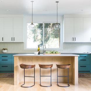 サンフランシスコの中くらいのミッドセンチュリースタイルのおしゃれなキッチン (フラットパネル扉のキャビネット、ターコイズのキャビネット、白いキッチンパネル、シルバーの調理設備、淡色無垢フローリング、ベージュの床、グレーのキッチンカウンター) の写真