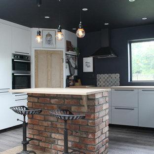 Idéer för ett mellanstort industriellt kök, med en rustik diskho, släta luckor, grå skåp, laminatbänkskiva, flerfärgad stänkskydd, stänkskydd i terrakottakakel, rostfria vitvaror, laminatgolv och en köksö
