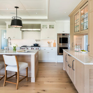 Photo of a beach style l-shaped kitchen in Providence with a farmhouse sink, white cabinets, white splashback, subway tile splashback, stainless steel appliances, light hardwood floors, with island, beige floor, white benchtop, timber and recessed.