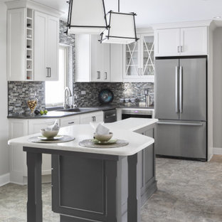 Design ideas for a large transitional u-shaped eat-in kitchen in Milwaukee with an undermount sink, shaker cabinets, white cabinets, quartz benchtops, grey splashback, stone tile splashback, stainless steel appliances, vinyl floors, with island, grey floor and grey benchtop.