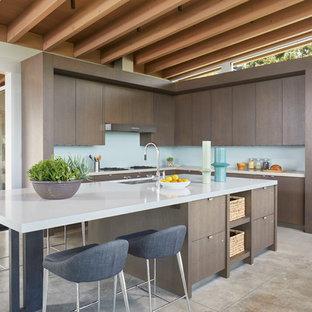 シアトルの大きいモダンスタイルのおしゃれなキッチン (アンダーカウンターシンク、フラットパネル扉のキャビネット、中間色木目調キャビネット、クオーツストーンカウンター、青いキッチンパネル、ガラス板のキッチンパネル、シルバーの調理設備の、コンクリートの床、グレーの床、グレーのキッチンカウンター) の写真