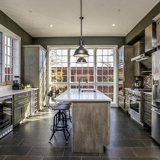 ボルチモアのインダストリアルスタイルのおしゃれなアイランドキッチン (アンダーカウンターシンク、シェーカースタイル扉のキャビネット、ヴィンテージ仕上げキャビネット、グレーのキッチンパネル、ボーダータイルのキッチンパネル、シルバーの調理設備の) の写真