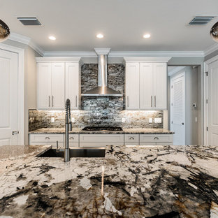 Inspiration for a mid-sized eclectic l-shaped eat-in kitchen in Tampa with an undermount sink, shaker cabinets, white cabinets, onyx benchtops, glass tile splashback and with island.