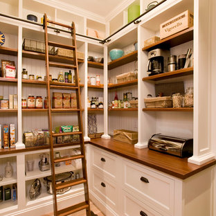 Coastal kitchen pantry designs - Example of a beach style kitchen pantry design in Boston with shaker cabinets, white cabinets, wood countertops and stainless steel appliances